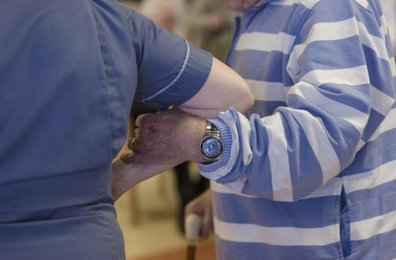 Nurse taking the arm of a man with Parkinson's