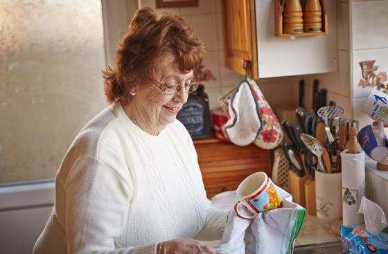 An older woman who has Parkinson's, drying up in her kitchen