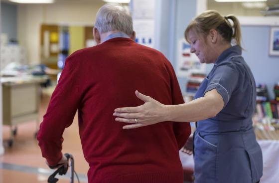 Man with Parkinson's being helped by a nurse