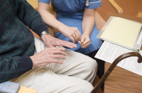 Image of the hands of man with Parkinson's and nurse