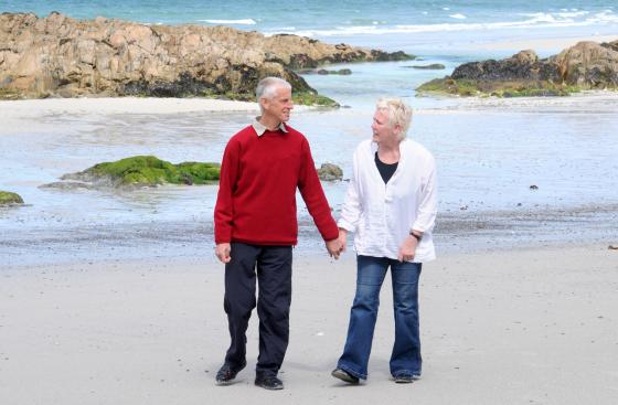 A woman with Parkinson's and her husband, walking along a beach holding hands
