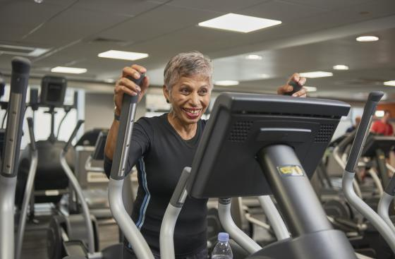Image of smiling woman using cross-trainer machine at gym
