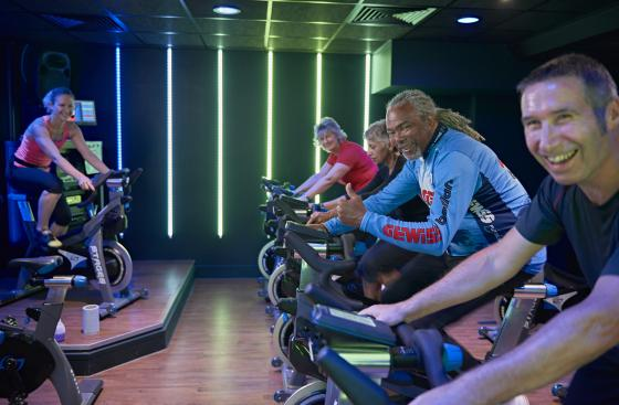 Image of people smiling using exercise bikes in gym class