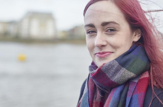 Emma Lawton, a young person with Parkinson's, in front of the River Thames