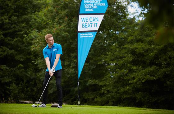 Playing golf in front of a blue Parkinson's UK banner