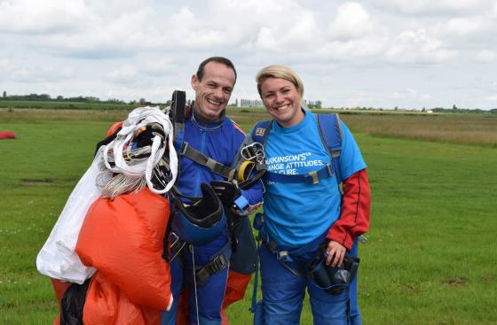 A Parkinson's UK skydiver smiles with her instructor after successfully completing her skydive