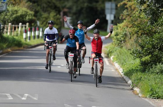 Group of cyclists with hands in the air