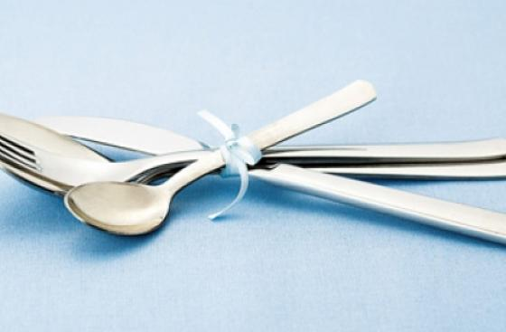 Fancy cutlery tied together with a bow, on a pale blue background