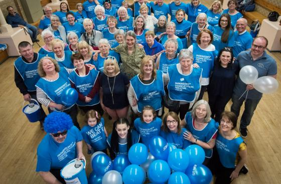A big crowd of Parkinson's UK volunteers, wearing their t-shirts and holding fundraising buckets