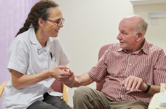 A person with Parkinson's sitting with a health and social care professional in hospital.