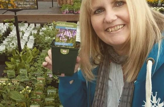 Michelle holds up a plant at her local garden center