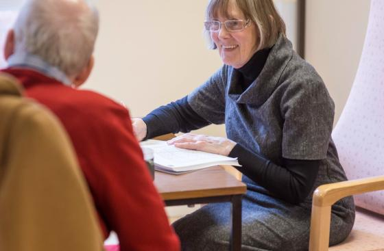 A healthcare professional sitting across a table from a person with Parkinson's, helping him with paperwork