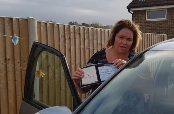 Lisa Sadler holds up her blue badge, standing next to her car