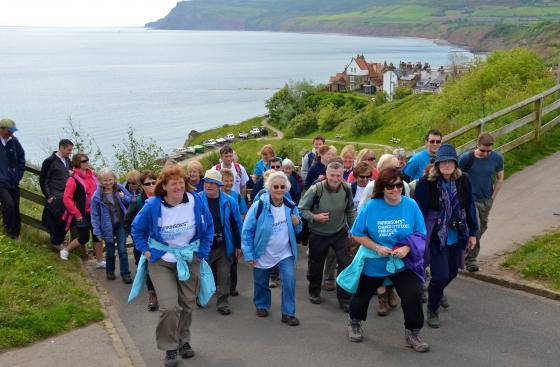 A group of people walk up a hill, they are wearing Parkinson's UK t-shirts, smiling and laughing. Behind them a beautiful bay stretches out, you can see one or two boats.