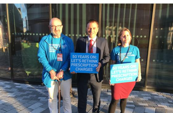 "Three Parkinson's UK campaigners, standing outside, two are holding signs that say ""50 years on: let's rethink prescription charges"""