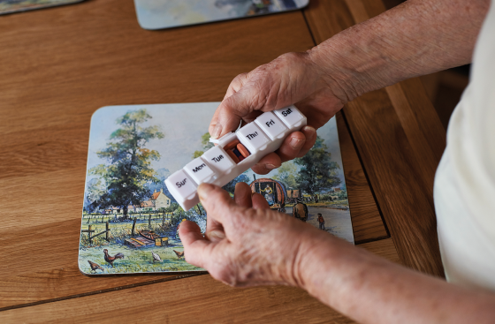 A person's hands holding a pill box filled with tablets