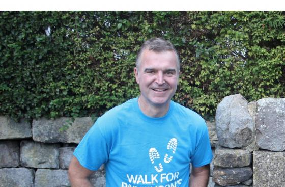 Dave Clark, Parkinson's UK's Champion of Walking, in his walk for Parkinson's T-shirt and walking boots
