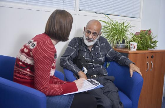 Person with Parkinson's speaking to a local adviser