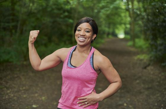 Woman outdoors in a wood wearing sports clothes, posing at the camera with one arm held in a power pose