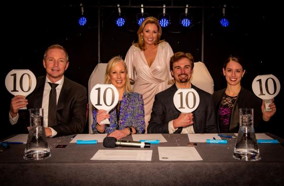 Four seated judges at Parkinson's does Strictly 2018, holding up perfect 10 score paddles, with celebrity Claire McCollum standing behind.