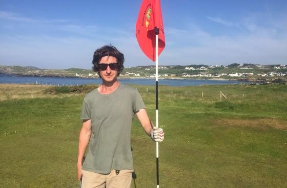 Mr Ronan Coyle, 37, at his home City of Derry Golf Club, holding the flag, standing on the golf course green.