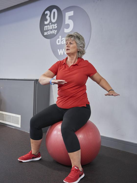Image of woman using exercise ball in gym