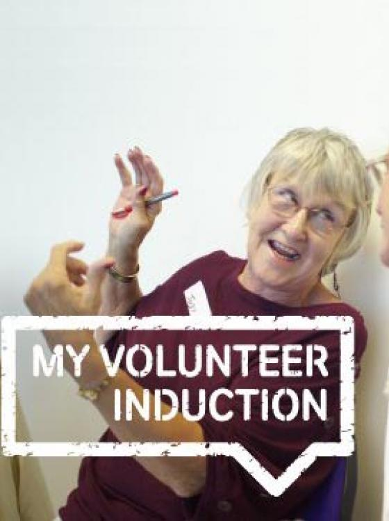 A picture of an older woman gesturing, talking to another woman. Overlayed with a speech bubble saying 'My Volunteer Induction'