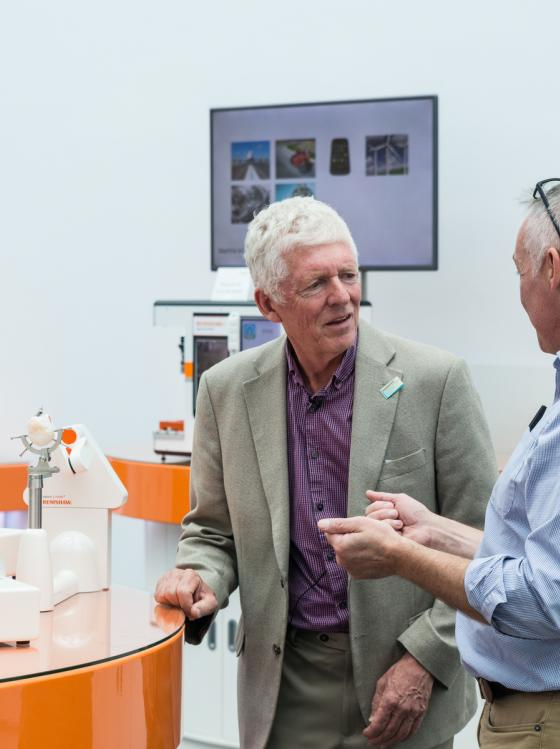 Tom Phipps, who has Parkinson's, talking to a scientist in the lab