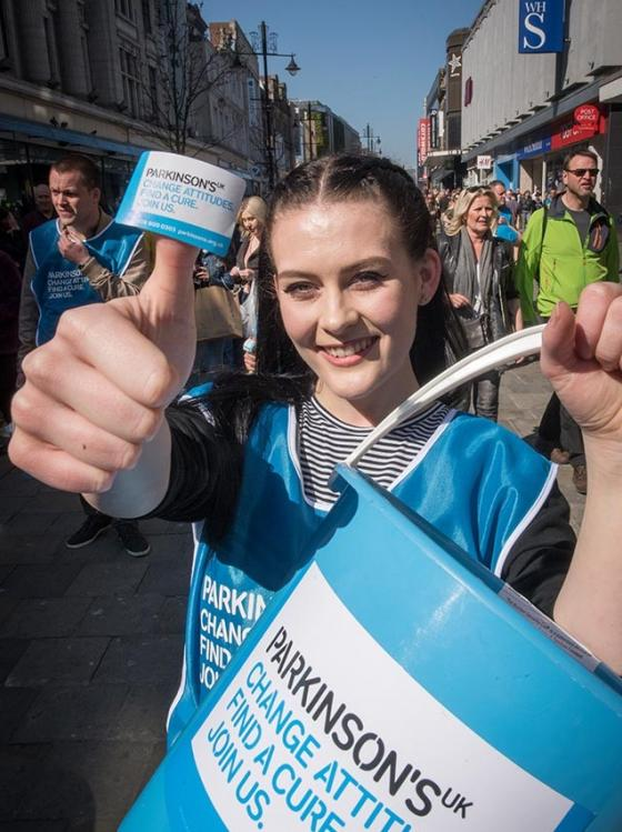 A woman holds up a Parkinson's UK collection bucket and sticker to the camera