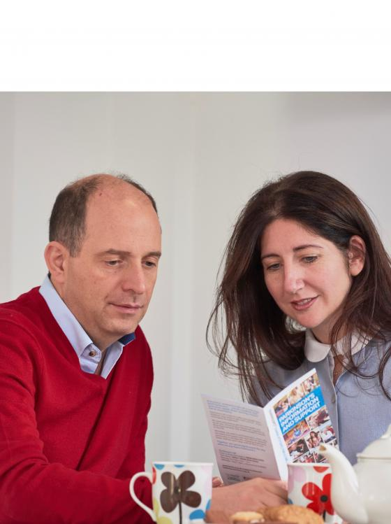 A couple reading Parkinson's UK information