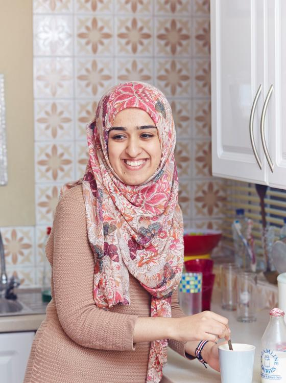 A young female carer making a cup of tea wearing a hijab
