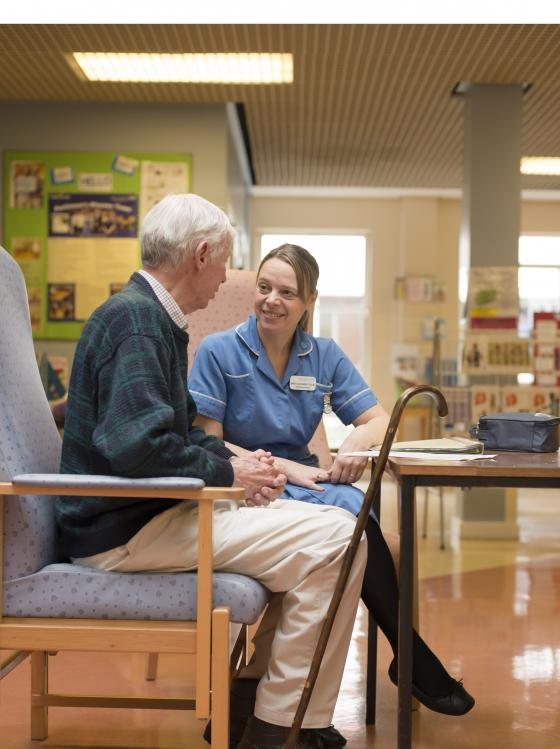 A man with Parkinson's in hospital speaking to healthcare professional