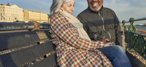 A working age man with Parkinson's and his partner laughing on a bench by the sea