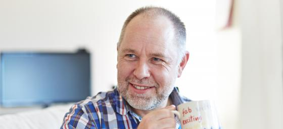 Paul, who has Parkinson's, holding a mug and smiling
