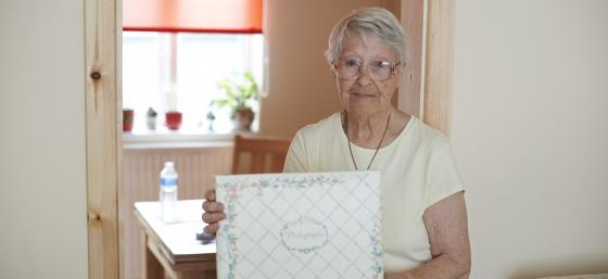 Rose, who has Parkinson's, holding a photo album