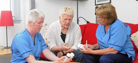 Sally, a person with Parkinson's, seeing her nurses
