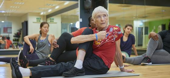 Image of an older woman stretching at an exercise class