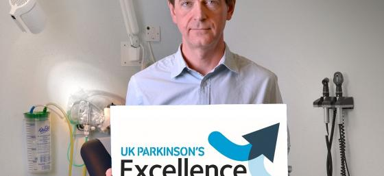 Donald Grosset holding an Excellence Network sign