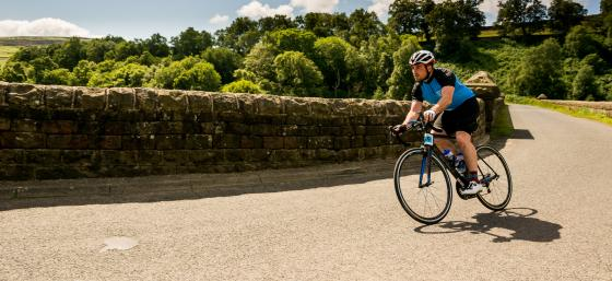 Parkinson's UK cyclist cycling around a bend in the road