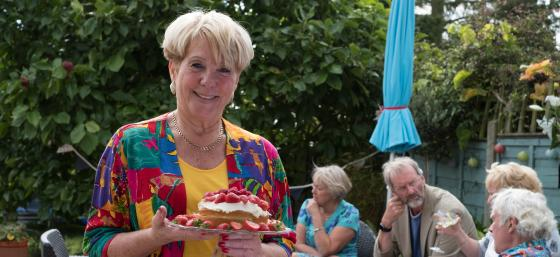 A woman holding a sponge cake at a Garden Gathering event