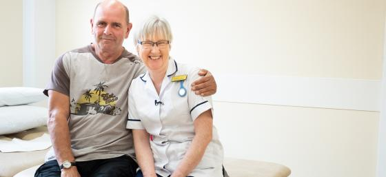 Ray and Fiona, his physiotherapist, sitting together on a medical bed