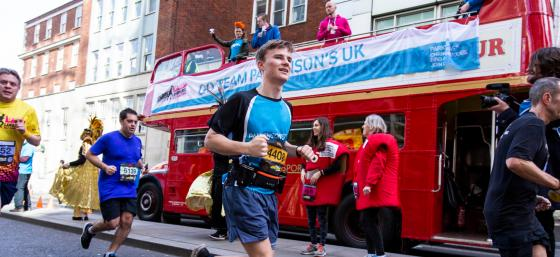 Runner smiling in front of London red bus with Parkinson's UK banner