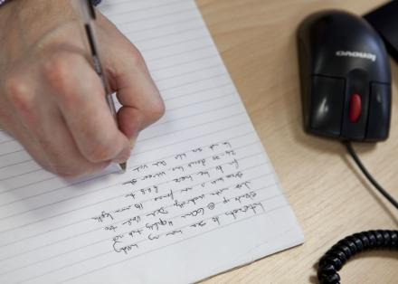 Person writing on lined paper