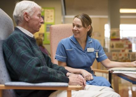 Image of an older man with Parkinson's talking to a health professional in hospital