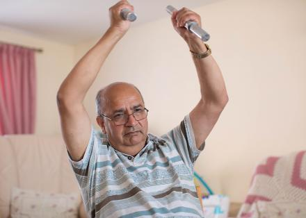 Image of a man doing chair-based exercise at home with small weights