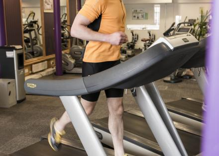 Younger man with Parkinson's using running machine in gym
