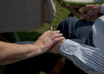 A close up of an older woman's hand resting on an older man's hand