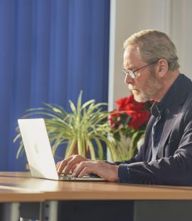 Peter, who has Parkinson's, using his laptop