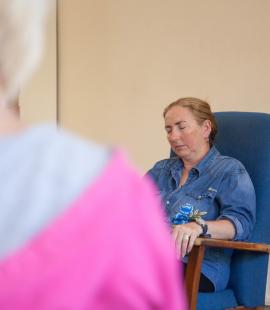 Sue Quy, who has Parkinson's, sitting in a chair and practising mindfulness