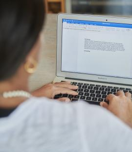 Omotola, a young woman with Parkinson's, typing on a laptop